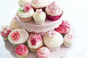 Pink cup cakes on stand.