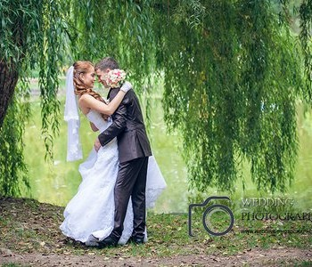 Bride and groom under the willow tree.