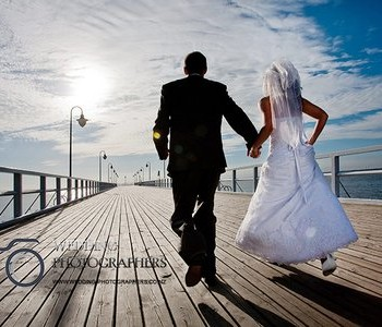 Bride and groom running on the pier.