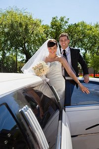 Bride and groom with wedding car.