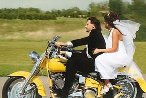 Just married leaving on motorbike.