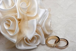 wedding decorations and wedding ring on on colored background