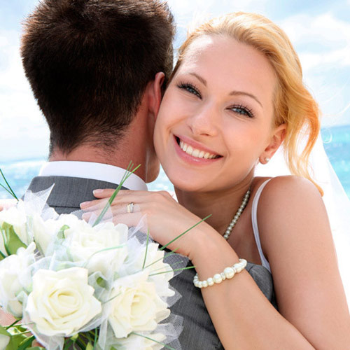 Wedding couple hugging with white flower bouquet.